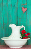 Antique water pitcher and basin with red flowers by weathered green wood background Stock Photos