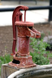 Antique Water Pump. An antique, rusty red water pump stock photo