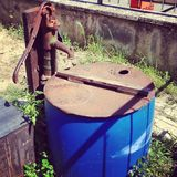 Antique water pump. With blue cistern in garden Stock Images