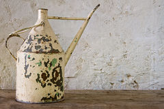 Antique watering can on a wooden table Royalty Free Stock Photo