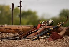 Antique weapons lying on the ground. Arrows, bow, saber lying on a wooden brown log royalty free stock photography