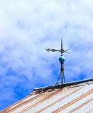 Antique Weather Vane. An old copper weather vane and lightning rod on top of a barn stock images