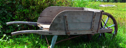 Antique wheelbarrow. Old wooden wheelbarrow in rural Maine antique store Stock Photos