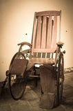 Antique Wheelchair. Antigue Wheelchair in an abandoned hospital Royalty Free Stock Photography