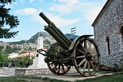 Historical Canon on Display, Kalavryta Church, Peloponnese, Greece. An antique wheeled field gun or canon on display outside the Orthodox Cathedral Church of stock image