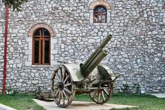 Historical Canon on Display, Kalavryta Church, Peloponnese, Greece. An antique wheeled field gun or canon on display outside the Orthodox Cathedral Church of stock photo
