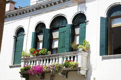 Antique white building with green wooden windows with  in Venezia Royalty Free Stock Image