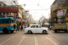 Antique white car down the busy street. Antique white Ambassador car down the busy street in Kolkata, India. First Ambassador was produced by the Yellow Cab Royalty Free Stock Images
