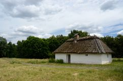 Antique white clay house with hay roof in Pirogovo park, Kiev stock photos