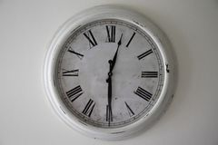 Antique white clock face on a white wall. Antique white clock face wall roman numerals 12.30 stock photo