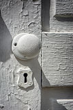 Antique White Doorknob. A detailed close up of an antique white doorknob and skelleton keyhole built in the late 19th or early 20th century stock image