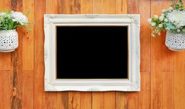 Antique white photo frame with black empty space for your picture or text placed on wood plank wall background stock image