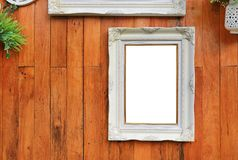 Antique white photo frame with empty space for your picture or text placed on wood plank wall background.  stock photography