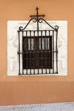 Antique window with wrought iron grille Royalty Free Stock Image