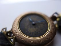 Antique woman`s watch closeup gold case. Blackened dial filigree engraved Stock Images