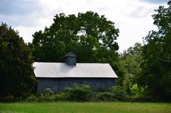 Antique wood barn with cupola  in countryside Royalty Free Stock Photography