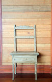Antique wood chair against wooden wall Stock Photography