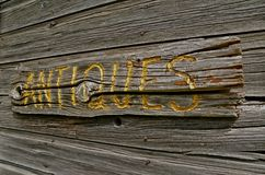 Antique Wood Sign. ANTIQUES has been carved into a piece of old weathered wood and placed on a siding of weathered wood Royalty Free Stock Photos