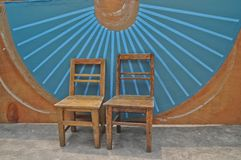 Antique wooden basic chairs and blue Chinese fan wall background Royalty Free Stock Photos