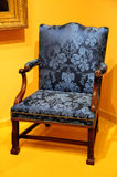 Antique wooden chair. Close up antique wooden chair with blue covering in corner of orange room Royalty Free Stock Image