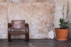 Antique wooden chair. In front of old grunge bare cement mortar wall. Chinese interior design royalty free stock images