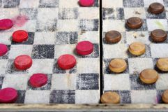 Antique wooden checkers board game. Vintage wooden red and brown checkers on old board game royalty free stock photography