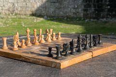 Antique wooden chess board on a wooden table outdoor, strategic activity in the open air. Space for text Stock Image