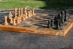 Antique wooden chess board on a wooden table outdoor, strategic activity in the open air. Space for text Royalty Free Stock Photos