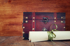 Antique wooden chest with old parchment on wooden table Stock Photos
