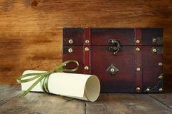 Antique wooden chest with old parchment on wooden table Royalty Free Stock Images