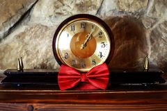 Antique wooden clock and red butterfly for the groom on a stone background, morning of the groom, wedding accessories.  Stock Image