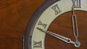 Antique wooden clock, almost twelve. Close up view of a quarter face of antique wooden clock with Roman numerals showing time approaching 12 midday or midnight stock video footage