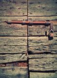 Antique wooden door with lock and padlock. Worn and worn wood, rusty lock royalty free stock photo