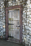 Antique wooden door in a stone wall Royalty Free Stock Photo