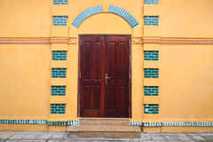 Antique wooden door and yellow wall. At Ho Chi Minh's Residence Stock Photos