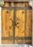 Antique antique wooden doors with forged handles, rivets and rungs. Antique massive wooden doors with wrought handles, rivets and crossbars illuminated by bright stock photography
