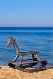 Antique Wooden horse toy on the beach. Wooden horse, rocking horse, antique toy on the beach feel lonely, childenhood concept Stock Photo