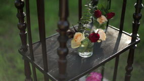 On the antique wooden stand tiny bouquets of roses. In glass vases stock video
