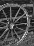 Antique wooden wagon wheel against wooden barn. stock photos
