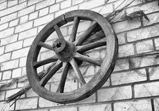 Antique wooden wagon wheel hanging on a brick wall. Royalty Free Stock Images