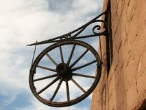 Antique wooden wagon wheel hanging on a wall as a decoration. Royalty Free Stock Photos