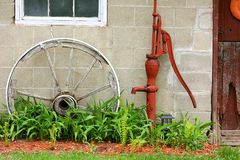 Antique Wooden Wagon Wheel and Water Pump by Barn Stock Image