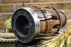 Antique wooden wheel hub. On burlap sack against rural brick wall with oregano, whole wheat Stock Photo