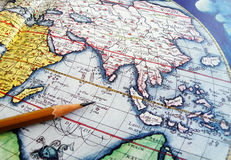 Antique world globe with pencil. Exotic travels and tourism theme photo. An image of an old world map beautifully colored, showing the region of asia, Arabia Royalty Free Stock Photography