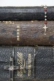 Three Antique Stacked Bibles with Two Antique Crosses Rosary on. Antique worn leather Bibles in a close up stack with antique rosary and antique cross made of royalty free stock photo