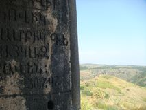 Antique writings in Armenian with after all a hilly arid landscape. Stock Photography
