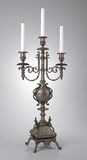 Candle. Antique wrought iron candlestick on a gray background Royalty Free Stock Photography