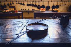Antique XIX century old kitchen with tools, pans, pots and food ingredients. All over che benches and tables royalty free stock photo