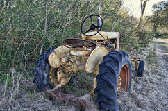 Yellow Rusted Tractor. An antique yellow, rusted, farm tractor along a cow path Royalty Free Stock Photography