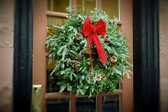 Antiqued Christmas Wreath hanging on door. Christmas wreath hanging in window of brick apartment building with flower box below, antiqued colors Royalty Free Stock Photos